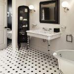 Baños clásico con suelo de mármol y lavabo con consola de metal cromado.