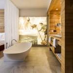 Cabecero de cama y zona de baño en listones de madera maciza.