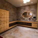 combinación de paredes y suelos en piedra natural y mobiliario de baño en madera.