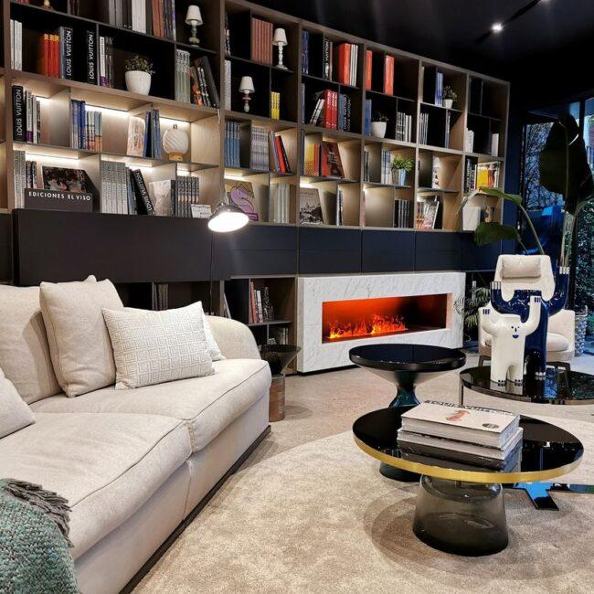 Bibliobar de diseño con sofá en tonos grises y estantería con muchos libros
