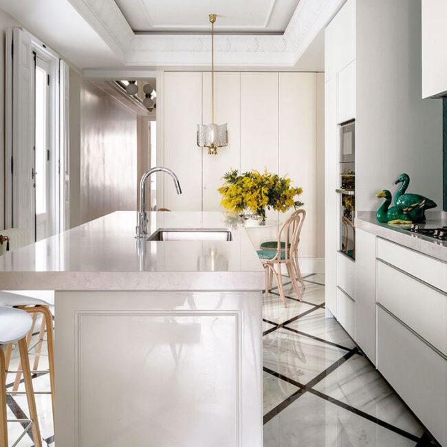 plano detalle de la cocina de diseño donde se ven la grifería, los taburetes y el suelo.