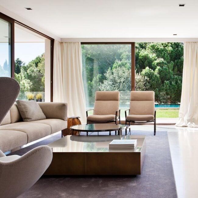 Salón de lujo con vistas al jardín y decorado con butacas y mobiliario exclusivo