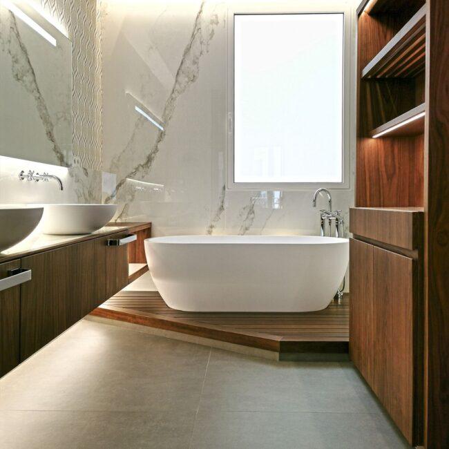 baño de madera con bañera exenta de diseño y lavabos a juego