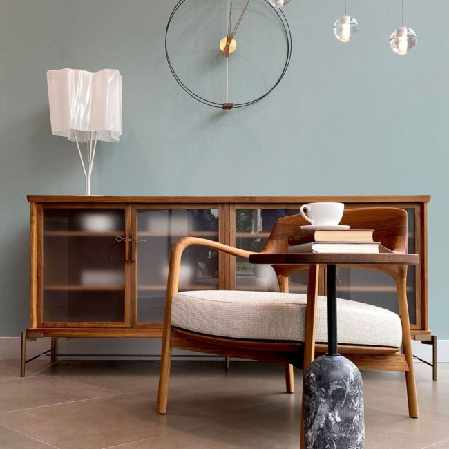 butaca de diseño rústico en madera con cómoda del mismo estilo sobre pared de tonos azules.