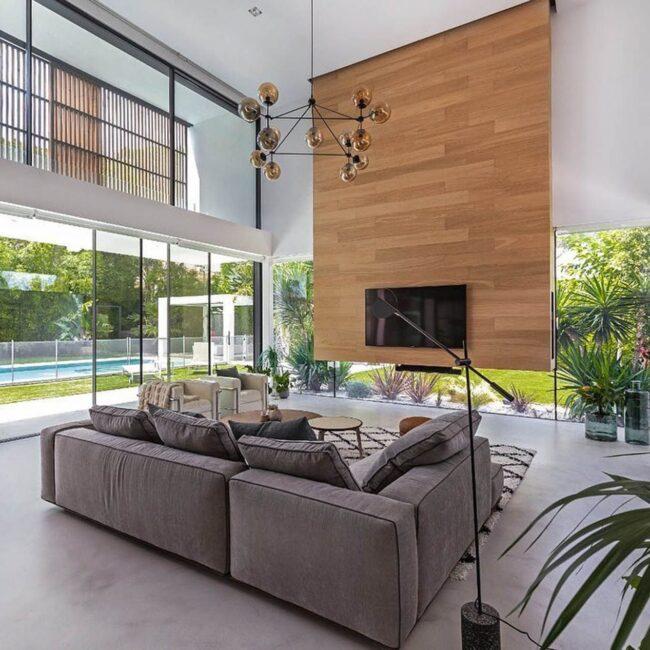salón de diseño con sofá en tonos grises y amplios ventanales con vistas al jardín