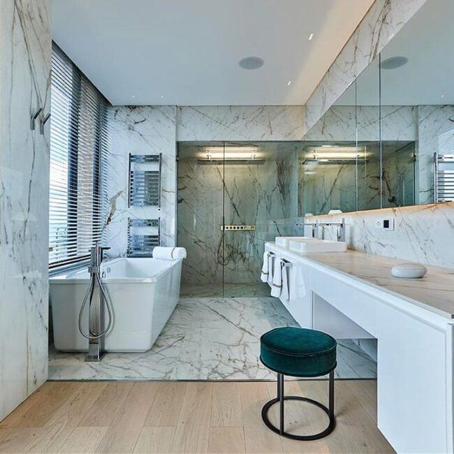 frontal del baño en la que se ve la bañera exenta en color blanco, la zona de lavabos con tocador incluido, y al fondo la ducha con acabado en mármol